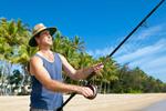 Man holding a fishing rod on a tropical beach