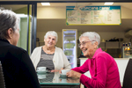 Elderly women smiling and chatting over coffee at a retirement village cafe