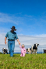 Farmer walking with his young daughter in the green pastures of a dairy farm
