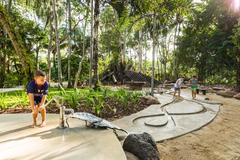 A kid pumping water in a Natures Play playground with other kids in background