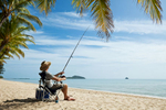 Man sitting in a chair at tropical beach holding a fishing rod