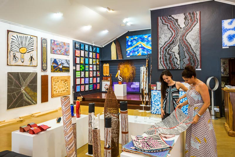 Shop assistant helping a woman shopping in an indigenous art gallery