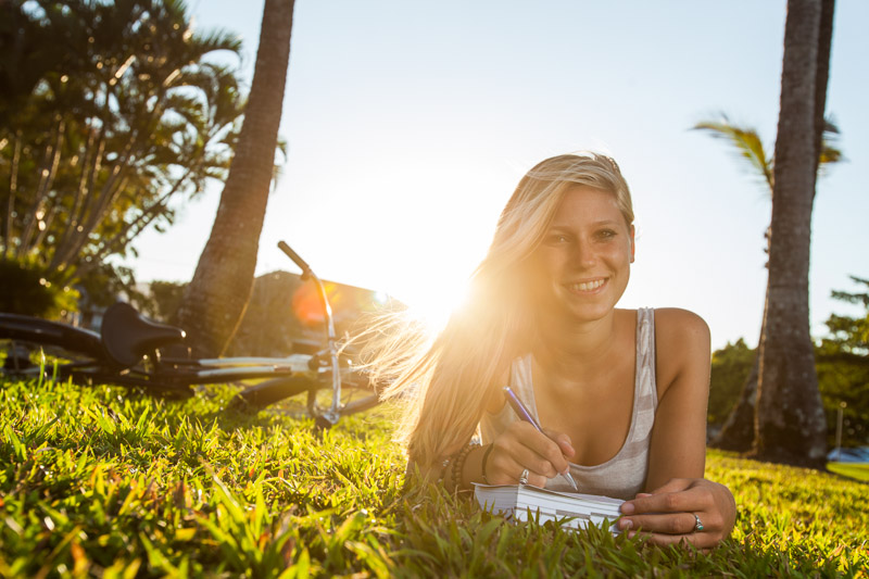 Young woman lying on grass writing postcards with the sun setting behind