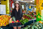Young woman holding a tray of fruit and vegetables in Rustys Markets, Cairns