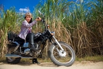 Portrait of woman seated on motorcycle in front of canefields, Cairns
