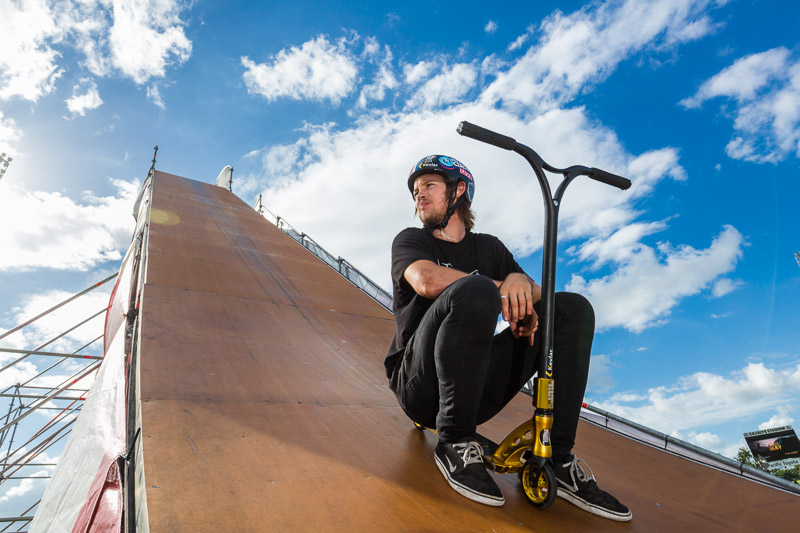 Portrait of extreme scooter rider Ryan Williams sitting on jump ramp, Cairns