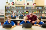 A teacher helping kids working with laptops by photographer in Cairns