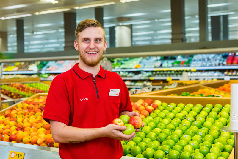 Business portrait of staff member in produce section of Coles Earlville, Cairns