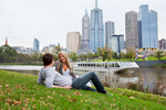 Young couple relaxing on the grassy riverside with city skyline beyond