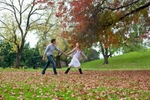 Young couple holding hands and walking through autumn leaves in a park