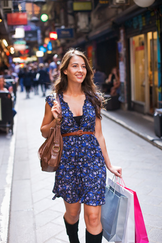 Fashionable young woman walking down city laneway carrying shopping bags