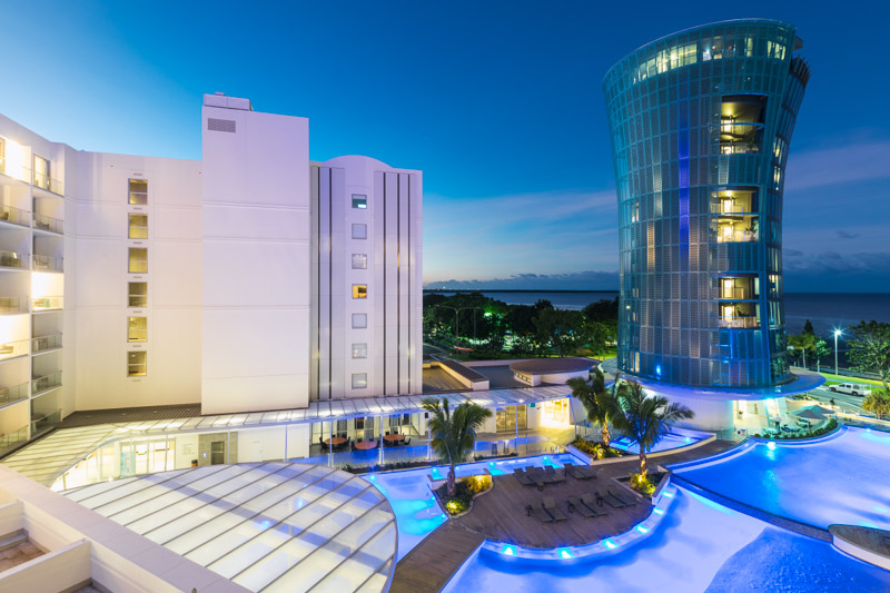 Elevated view of Riley Hotel pool and tower illuminated at twilight, Cairns
