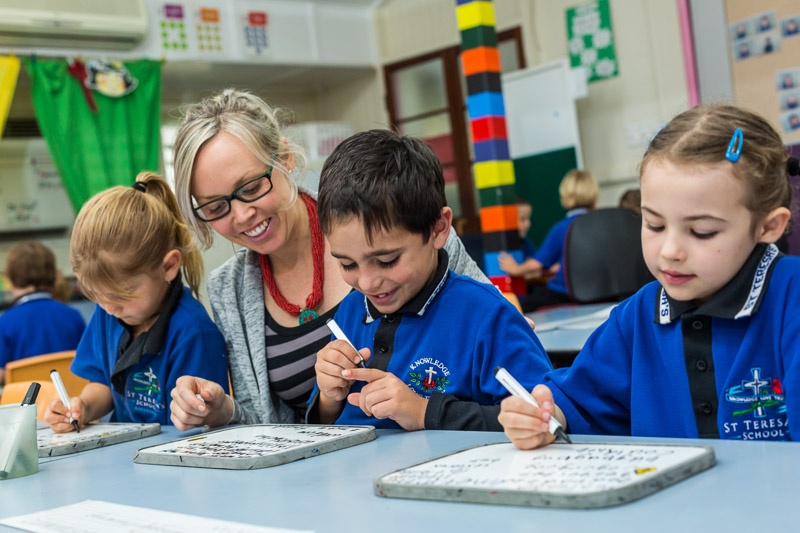 Portrait of a teacher helping young students with their writing skills