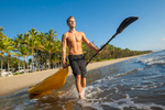 Young man walking with his kayak out into water at beach