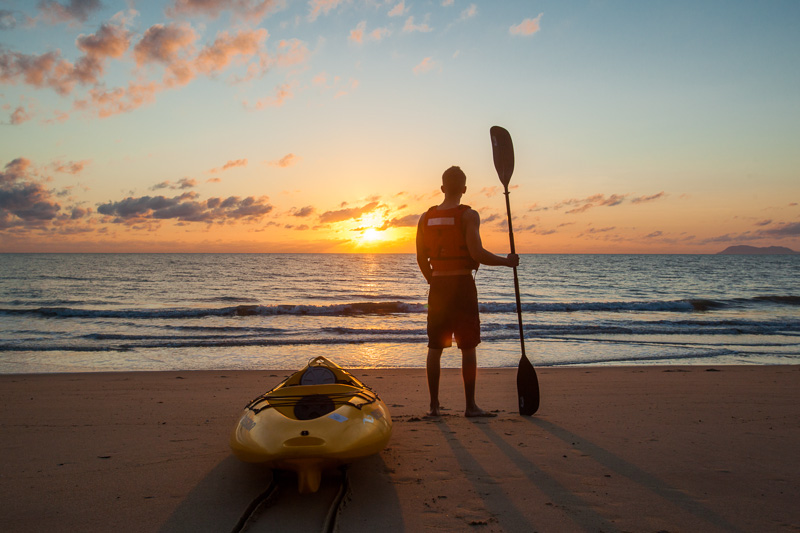 A man with paddle standing next to a kayak looking out to sea at sunrise
