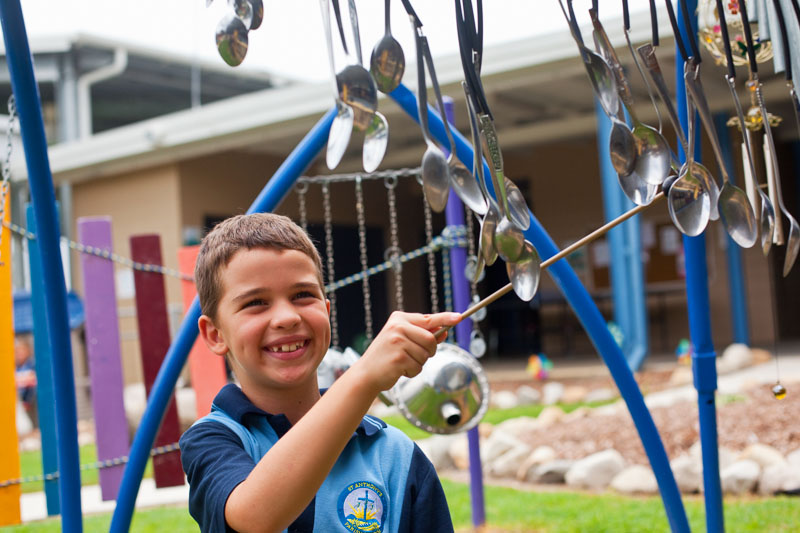 Portrait of young male student playing with a musical activity in the playground