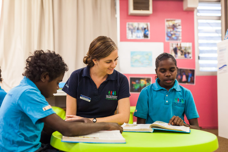 Teacher and aboriginal students reading in the classroom, Cape York