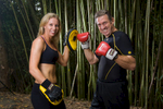 Portrait of female fitness trainer with male client in boxing gloves
