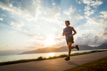 Young man running along the waterfront with sunrise beyond