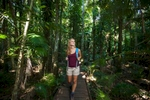Young woman walking with backpack through rainforest boardwalk