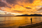 Fisherman standing in water is silhouetted against sunrise sky