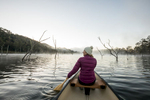 View of a woman paddling a canoe on a misty lake at sunrise