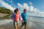 Mature couple walking along Four Mile Beach looking out to sea