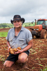 Portrait of a potato farmer holding some harvested potatoes, Atherton Tablelands