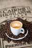 A cup of coffee and roasted coffee beans from the Cairns Highlands