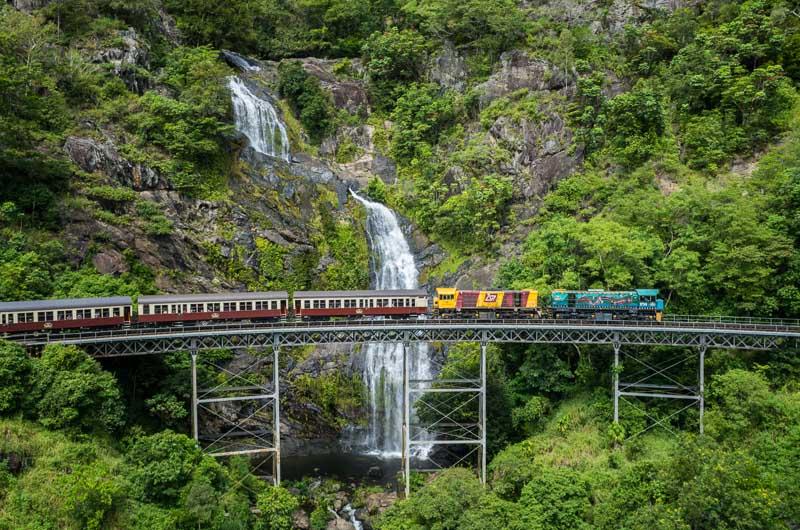 Aerial view of Kuranda Scenic Railway train crossing Stoney Creek Bridge and waterfall