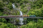 Aerial view of Kuranda Scenic Railway train crossing Stoney Creek Bridge and waterfall