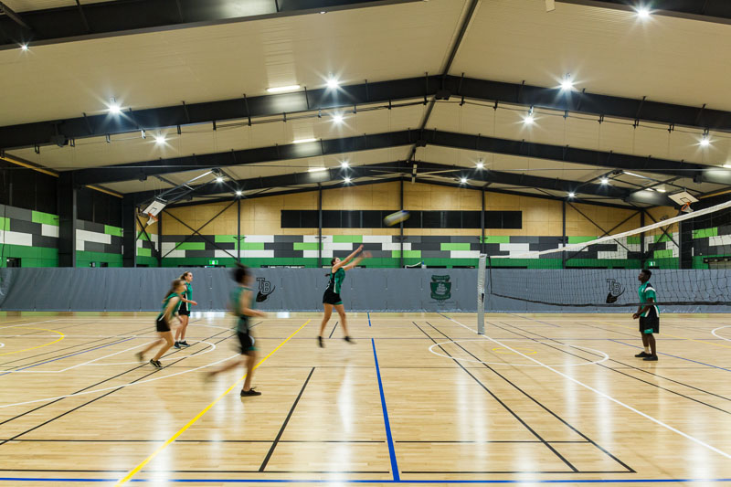 Children playing volleyball in high school sports hall, Cairns