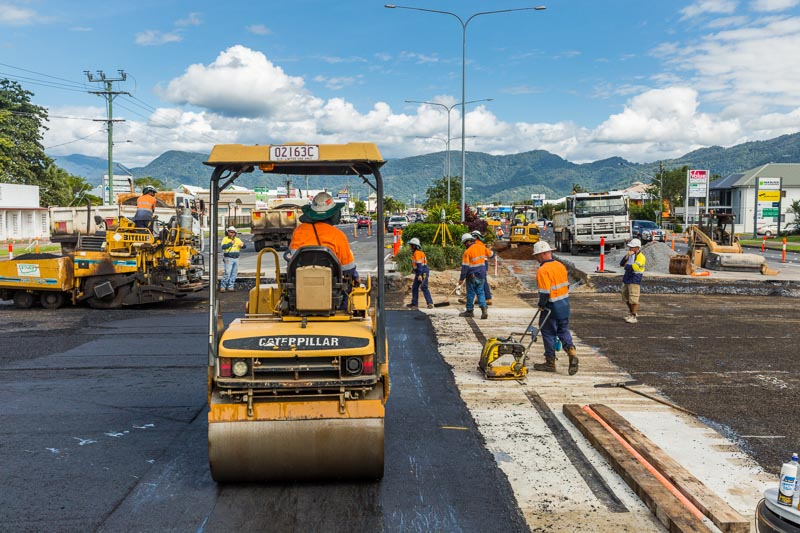 Road workers laying bitumen on a road construction project, Cairns