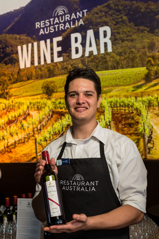 Barman offering wine tasting at 2014 Australian Tourism Exchange Farewell Function in Cairns