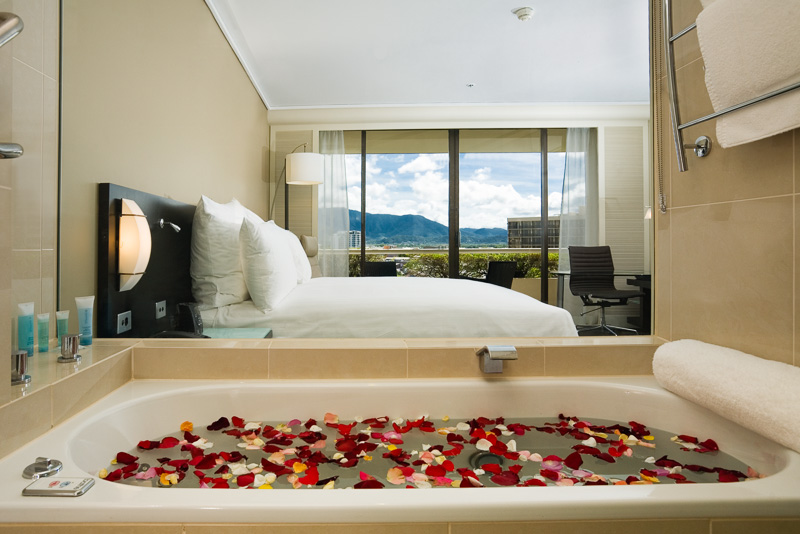 Bathtub with rose petals in hotel room at Hilton Cairns