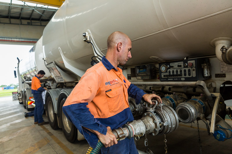 Men fitting hoses to a petrol tanker inside a workshop, Cairns