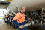 Men fitting hoses to a petrol tanker inside a workshop, Cairns