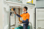 Tradesman doing electrical testing on fuel supply unit, Cairns