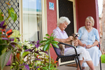 Aged resident with pet dog chatting to neighbour at assisted living community