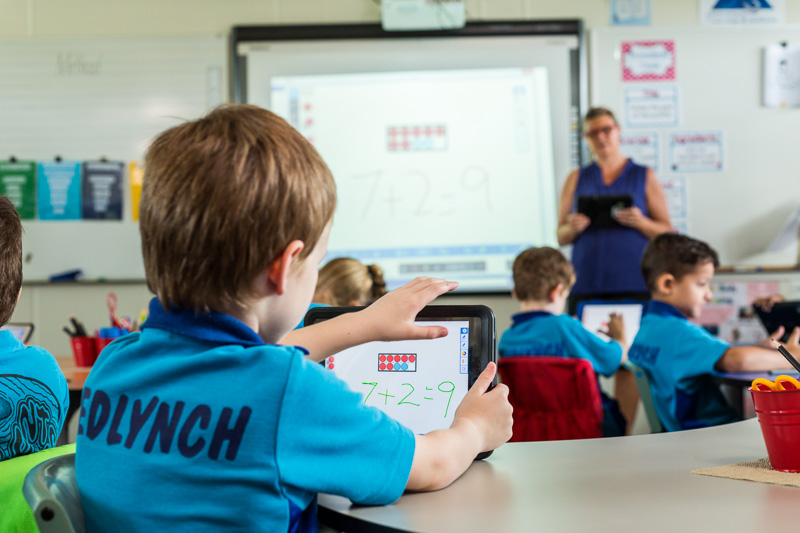 View over shoulder of young student learning maths on an iPad with teacher looking on