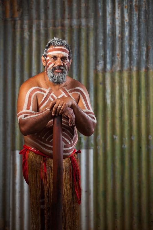 Male indigenous dancer in ochre paint standing with didgeridoo