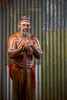 Male indigenous dancer in ochre paint standing with didgeridoo