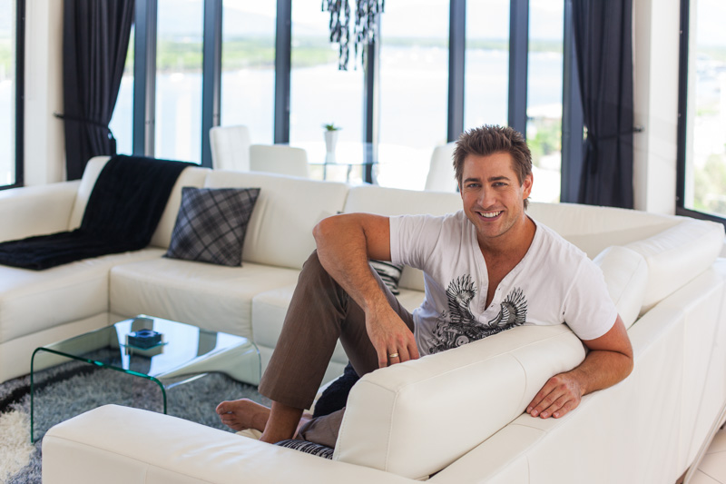 Portrait of illusionist Sam Powers sitting on lounge at home, Cairns