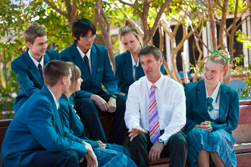 A high school principal talking with group of senior students