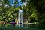 Woman relaxing on floating airbed looking at a tropical waterfall