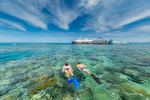 Couple snorkelling together on the Great Barrier Reef with reef pontoon in background
