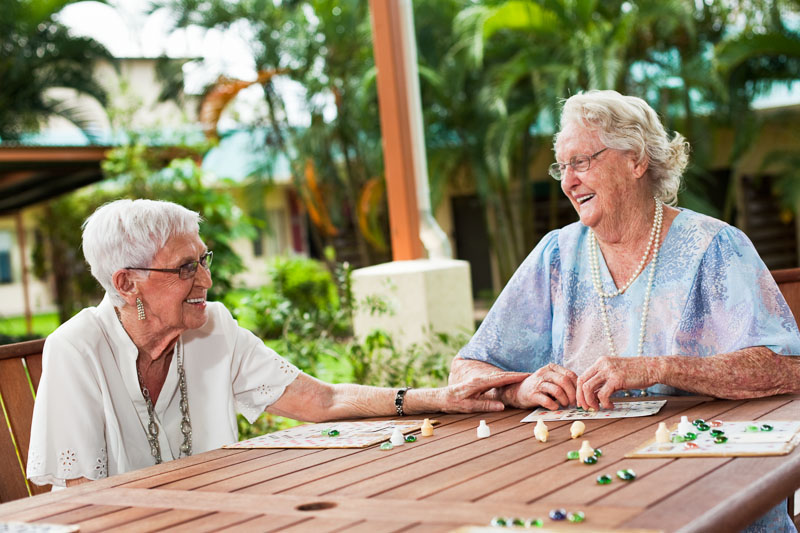 Elderly friends laughing together at New Horizons Villas in Cairns