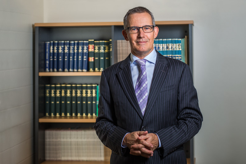 Environmental portrait of male lawyer in front of bookshelf, Cairns