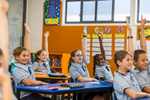 School students raise their hands to answer a question in the classroom