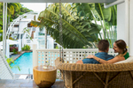 Couple relaxing in swing chair with pool in background at The Reef House, Palm Cove